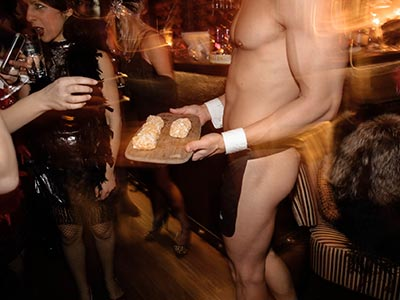 Topless waiters serving food at a hens party